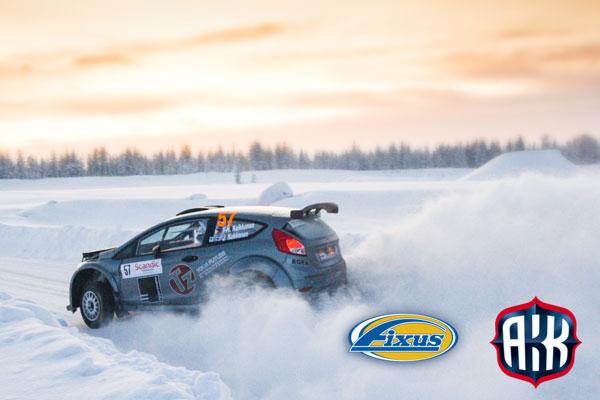 Ralliauto ajaa talvirallissa lumi pöllyten, mukana myös Fixus ja AKK logot.